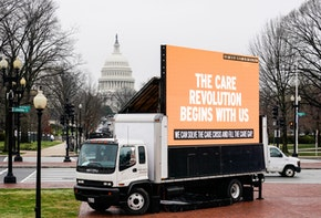 WASHINGTON, DC - MARCH 25: An LED display calling on Congress to invest in Care jobs sits in front of Union Station on March 25, 2021 in Washington, DC.  Members of the Service Employees International Union (SEIU) and National Domestic Workers Alliance (NDWA) project a pledge demanding that Congress prioritize caregiving in the next recovery package in an installation outside of the US Capitol. The pledge was signed by 17,574 caregivers, consumers and family members. (Photo by Jemal Countess/Getty Images for National Domestic Workers Alliance & Service Employees International Union )