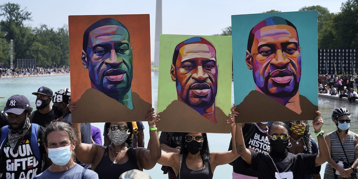 WASHINGTON, DC - AUGUST 28: Attendees hold images of George Floyd as they participate in the March on Washington at the Lincoln Memorial August 28, 2020 in Washington, DC. Today marks the 57th anniversary of Rev. Martin Luther King Jr.'s