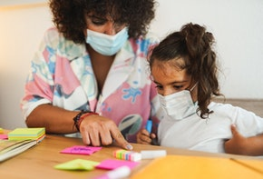 Mother doing home schooling with child while wearing surgical face mask for coronavirus