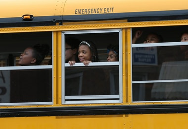 BALTIMORE, MD - MAY 01:  Children riding home from school on a school bus watch as Baltimore residents celebrate at the corner of West North Avenue and Pennsylvania Avenue after Baltimore authorities released a report on the death of Freddie Gray  on May 1, 2015 in Baltimore, Maryland. Marilyn Mosby, Baltimore City State's Attorney, ruled the death of Freddie Gray a homicide and that criminal charges will be filed. Gray, 25, was arrested for possessing a switch blade knife on April 12 outside the Gilmor Houses housing project on Baltimore's west side. According to his attorney, Gray died a week later in the hospital from a severe spinal cord injury he received while in police custody.  (Photo by Win McNamee/Getty Images)