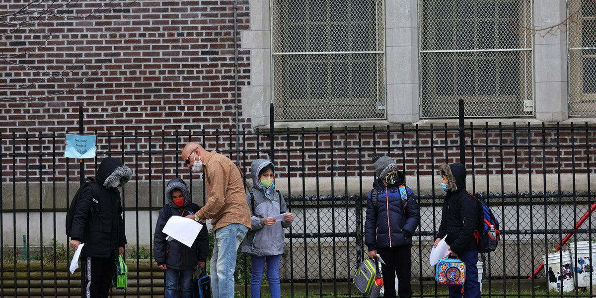 NEW YORK, NEW YORK - DECEMBER 07: Children returning to school line up before entering P.S. 179 Kensington on December 07, 2020 in New York City. The New York City public school system opened for in-person learning 10 days after being shut down by Mayor Bill De Blasio due to a rising number of coronavirus (COVID-19) positive cases in the city. (Photo by Michael M. Santiago/Getty Images)