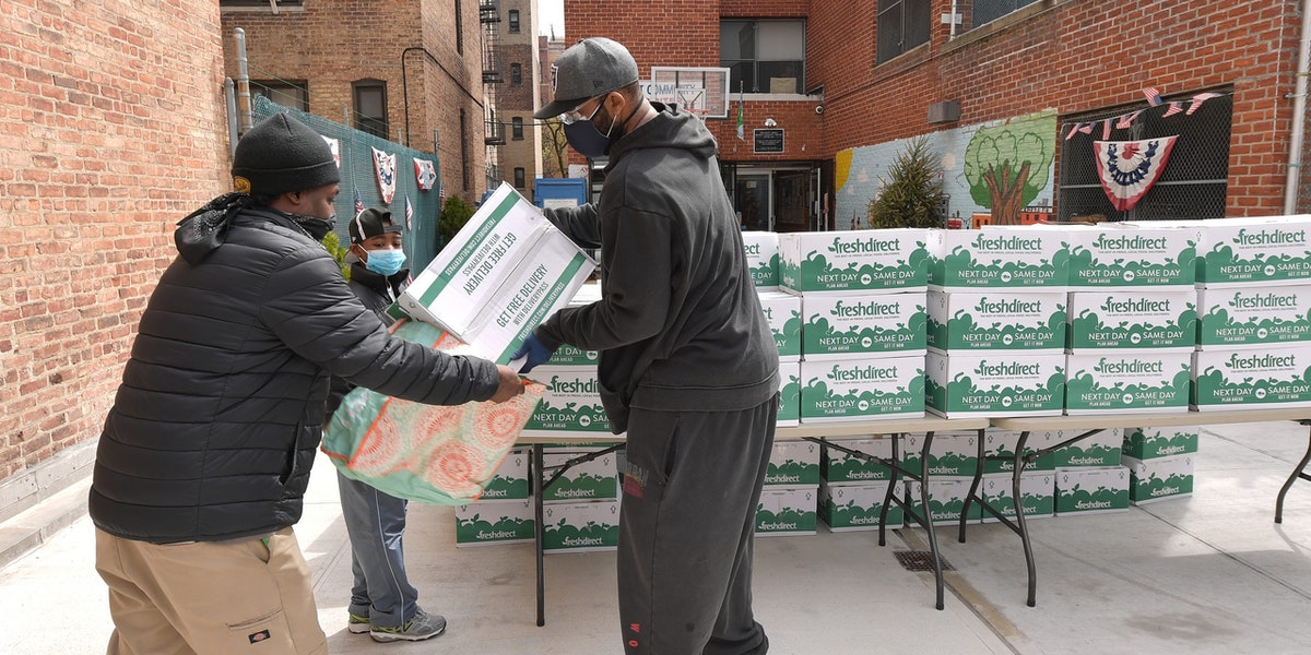 NEW YORK, NEW YORK - APRIL 08: Former professional baseball player CC Sabathia (R) distributes pantry boxes to Boys And Girls Club families at the Belmont Community Day Care Center on April 08, 2020 in The Bronx Borough of New York City. (Photo by Michael Loccisano/Getty Images)