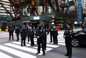 NEW YORK, NEW YORK - APRIL 02: NYPD officers stand watch after a person fell while climbing the side of a Chase Bank location as demonstrators gather in Midtown Manhattan on April 02, 2021 in New York City. Members of the Extinction Rebellion NYC and various organizations held a rally and a march in solidarity with the #StopTheMoneyPipeline coalition, urging President Joe Biden to stop the construction of the Line 3 pipeline in Minnesota. (Photo by Michael M. Santiago/Getty Images)