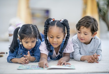 A group of three multi-ethnic preschool children lay on the floor intensely reading a story book together