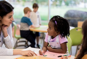 Caring female art teacher helps a young girl with her drawing during art class.