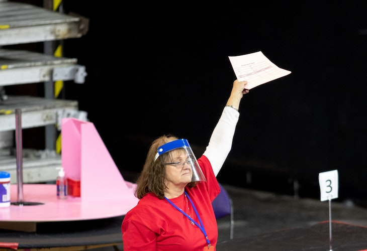PHOENIX, AZ - MAY 01: A contractor working for Cyber Ninjas, who was hired by the Arizona State Senate, works to recount ballots from the 2020 general election at Veterans Memorial Coliseum on May 1, 2021 in Phoenix, Arizona. The Maricopa County ballot recount comes after two election audits found no evidence of widespread fraud in Arizona.  (Photo by Courtney Pedroza/Getty Images)